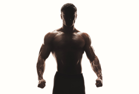 Foto de Dark silhouette of a strong man on white background. Confident young fitness man with strong hands and clenched fists. Clipping path inside - Imagen libre de derechos