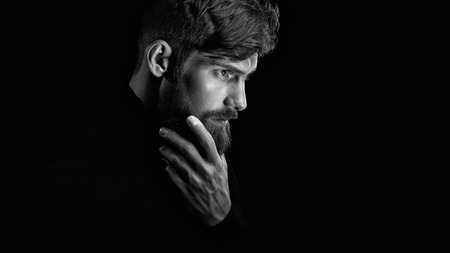 Photo pour Black and white image of attractive pensive young man looks into the distance stroking his beard over black background - image libre de droit
