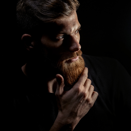 Photo for Portrait of young bearded man isolated at black background Guy with beard thoughtful, pensive, charming, looking forward Trendy hipster think of problem solving, finding solution - Royalty Free Image