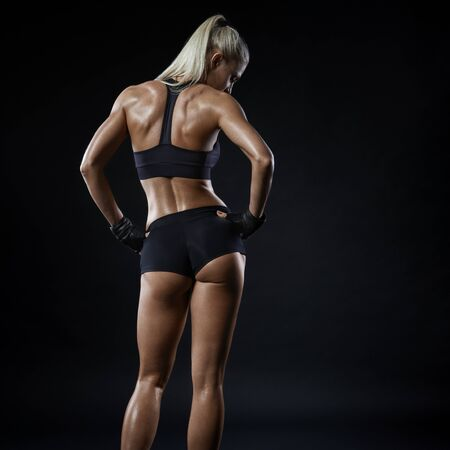 Foto de Fitness athletic young woman showing her well trained body, turned back. Image of sporty woman in sports clothing looking down relaxing. Energy fitness motivation concept. - Imagen libre de derechos