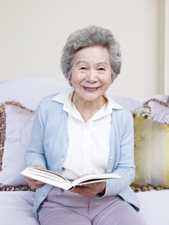 Photo for senior woman holding a book and smiling  - Royalty Free Image