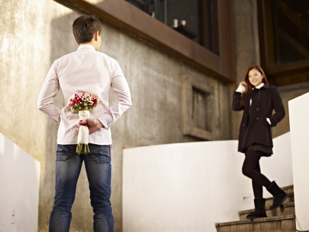 Photo for asian young man waiting by the steps with flowers behind back for his girlfriend  - Royalty Free Image