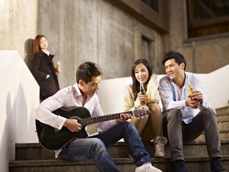 Foto de young asian friends lovers sitting on steps enjoying beer and music  - Imagen libre de derechos
