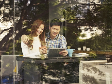 Photo for young couple sitting next to windows looking at tablet computer in cafe  - Royalty Free Image