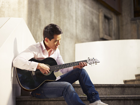 Photo for young man sitting on steps playing guitar and singing  - Royalty Free Image