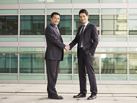 asian businessmen shaking hands looking at camera smiling.
