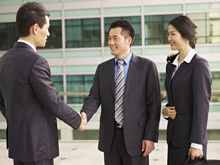 Photo for asian businesspeople shaking hands and smiling. - Royalty Free Image
