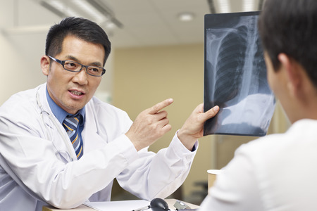 Foto de asian doctor talking to patient about x-ray result. - Imagen libre de derechos