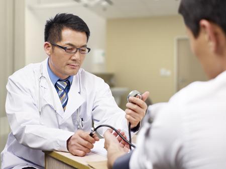 Foto per asian doctor measuring blood pressure of a patient. - Immagine Royalty Free