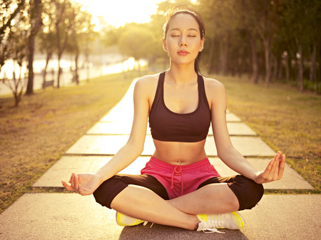 Photo pour young and beautiful asian woman practicing yoga outdoors in park in the warm light of sunset, meditation, fitness, healthy life and lifestyle concept. - image libre de droit