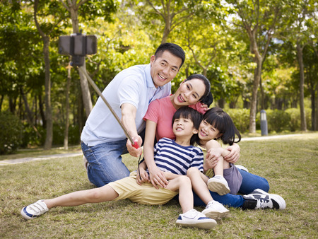 Foto de happy asian family with two children taking a outdoor selfie with selfie stick outdoors in a city park. - Imagen libre de derechos