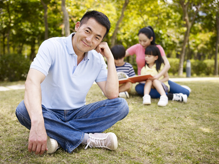 asian father sitting on grass happy and content with wife taking care of children in the background.