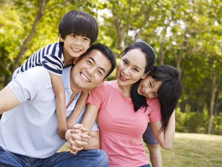 Photo pour asian family with two children taking a family photo outdoors in a city park. - image libre de droit