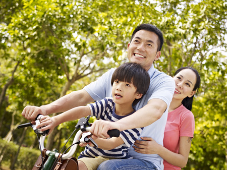 Photo pour mother father and son riding a bicycle together outdoors in a city park. - image libre de droit