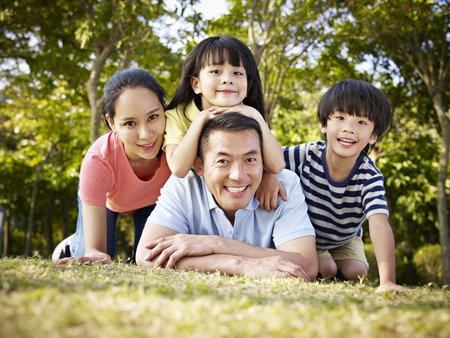 Photo for happy asian family with two children taking a family photo outdoors in a park. - Royalty Free Image