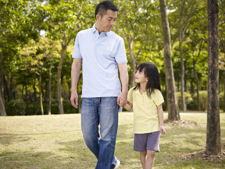 Photo for asian father and elementary-age daughter enjoying a walk in nature. - Royalty Free Image