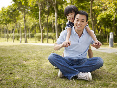 Photo for asian father and elementary-age son enjoying outdoor activity in park. - Royalty Free Image