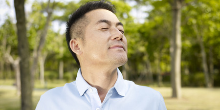 Photo for asian man enjoying a walk and fresh air in nature. - Royalty Free Image
