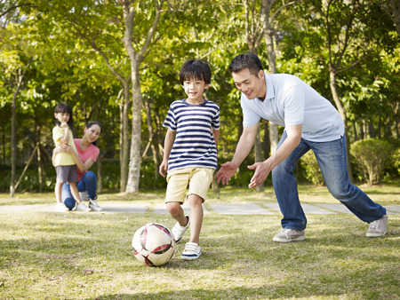 Photo pour asian father teaching son to play soccer (football) in a park - image libre de droit