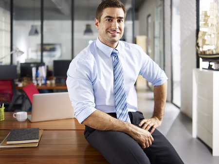 Foto de portrait of a smiling caucasian business executive sitting on desk in office. - Imagen libre de derechos