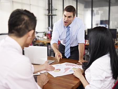 Foto de bad-tempered caucasian business executive yelling at two asian subordinates in office. - Imagen libre de derechos