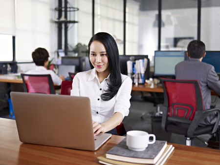 Photo for young asian businesswoman working in office using laptop computer with colleagues in background. - Royalty Free Image