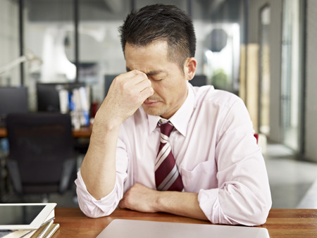 Photo pour asian businessman looking tired and frustrated in office. - image libre de droit