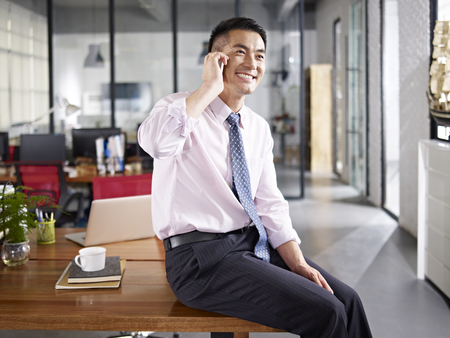 Photo for asian business person sitting on desk talking on mobile phone in office. - Royalty Free Image