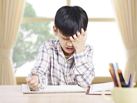Photo pour 10 year-old asian elementary schoolboy appears to be frustrated while doing homework at home. - image libre de droit