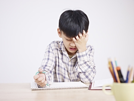 Photo for 10 year-old asian elementary schoolboy appears to be frustrated while doing homework. - Royalty Free Image