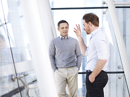 Photo for two caucasian business people having a casual conversation in modern office building. - Royalty Free Image