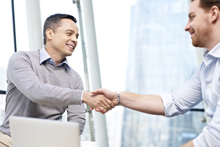 Photo for two caucasian businesspeople smiling and shaking hands in office. - Royalty Free Image