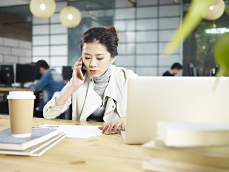 Photo for young asian office worker sitting at desk calling using mobile phone in office. - Royalty Free Image