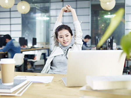 Photo for young asian business woman stretching upper body in office after task completed. - Royalty Free Image
