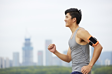 Foto per young asian male jogger with fitness tracker attached to arm running with skyline in the background. - Immagine Royalty Free