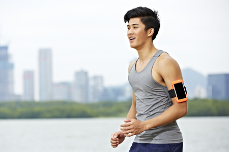 Photo pour young asian male jogger with fitness tracker attached to arm running with skyline in the background. - image libre de droit