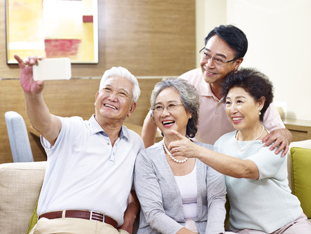 Photo pour two senior couples taking a selfie on couch at home - image libre de droit