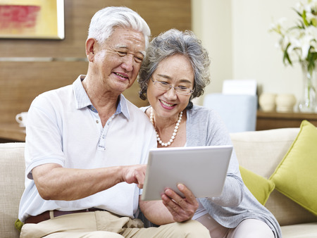 Photo for senior asian couple sharing a tablet computer at home - Royalty Free Image