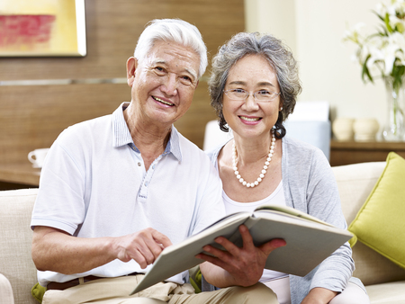 Foto de senior asian couple sitting on couch holding a book looking at camera smiling - Imagen libre de derechos