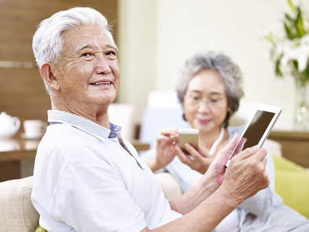 Photo for senior asian couple sitting on couch enjoying modern technology using tablet computer and cellphone - Royalty Free Image