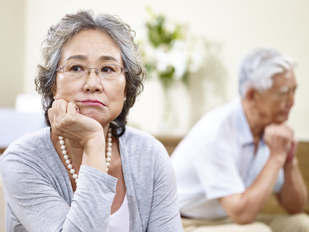 Photo pour senior asian couple sitting on couch at home, angry at each other - image libre de droit