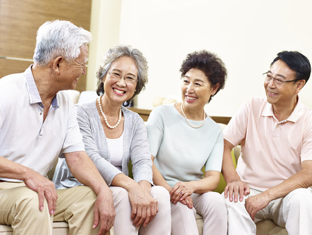 Photo pour two happy and active senior asian couples sitting on couch chatting smiling - image libre de droit