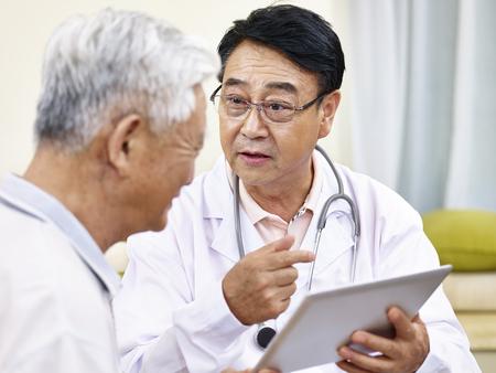 Foto de asian doctor explaining health condition to a senior patient - Imagen libre de derechos