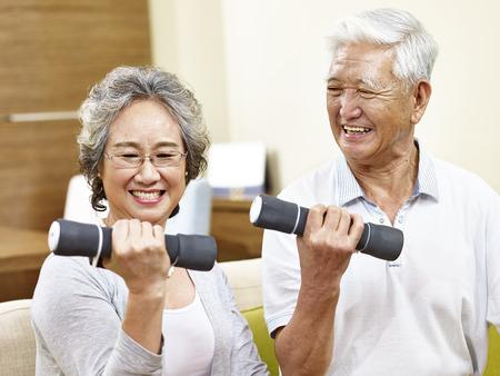 Photo for happy senior couple exercising using dumbbells, happy and smiling - Royalty Free Image