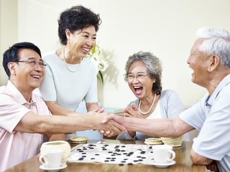 Photo pour senior asian men shaking hands  at the end of a weiqi game. - image libre de droit