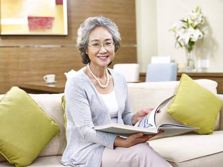 Foto de senior asian woman sitting on couch at home holding a book look at camera smiling. - Imagen libre de derechos