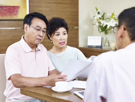 senior asian couple reading a sales contract appearing to be shocked.