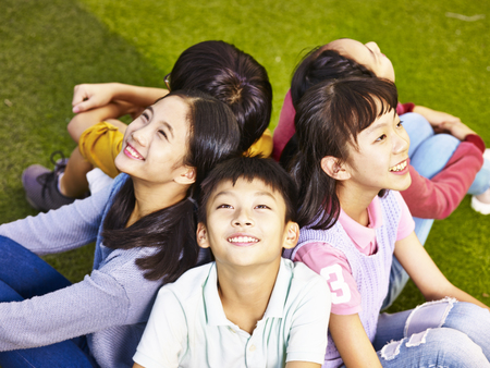 Foto de group of asian elementary school boys and girls sitting on playground grass looking up at the sky - Imagen libre de derechos