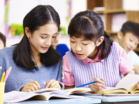 Photo for two asian elementary schoolgirls desk mates having a discussion during class in classroom. - Royalty Free Image