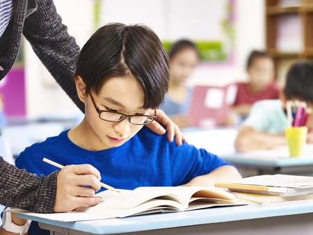 Foto de asian elementary school boy getting help from teacher in class. - Imagen libre de derechos